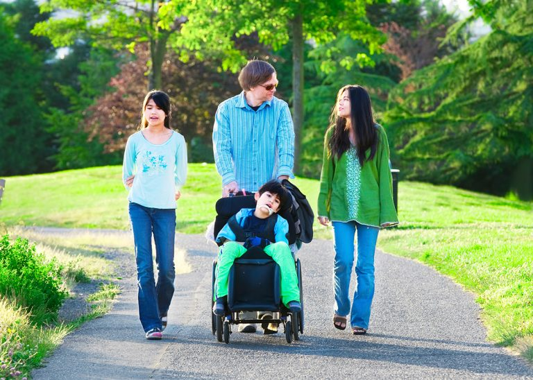 disabled child, father mother daughter and disabled son walking through a park